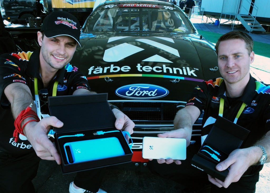 Kelowna based färbe technik entrepreneurs Shane Broesky, left and Steve Devries show off their exquisitely made and packaged mobile accessories against their NASCAR sponsored car